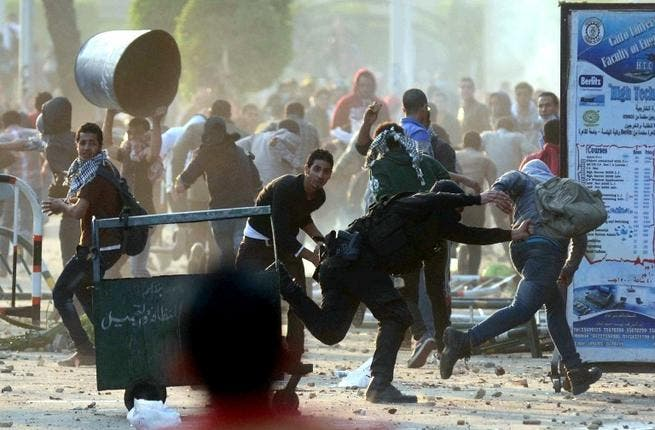 An Egyptian policeman tries to detain a student of Cairo University who support the Muslim Brotherhood during clashes with riot police in Cairo. [AFP]