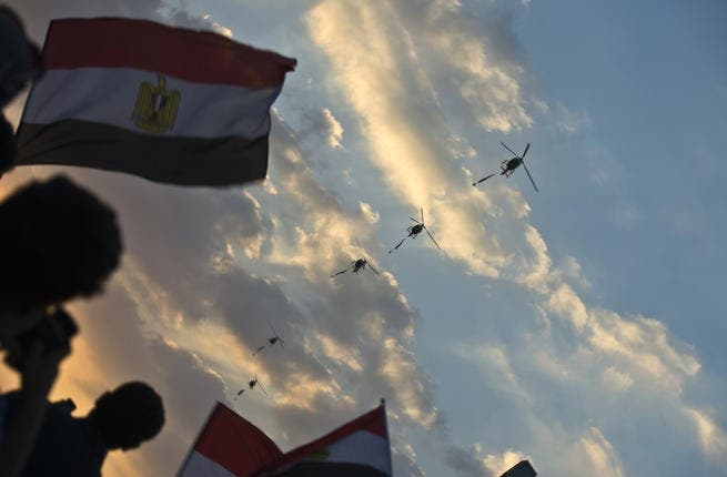 Egyptian army helicopters fly over as hundreds of thousands of Egyptian demonstrators gather outside the presidential palace in Cairo (Khaled Desouki / AFP)