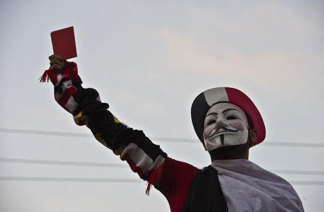 A protestor wearing a Guy Fawkes mask holds up a red card as thousands of Egyptian demonstrators gather outside the presidential palace in Cairo (Khaled Desouki / AFP)
