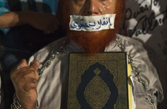 EGYPT, Cairo : An Egyptian man holds a copy of Quran and puts tape on his mouth with Arabic slogan