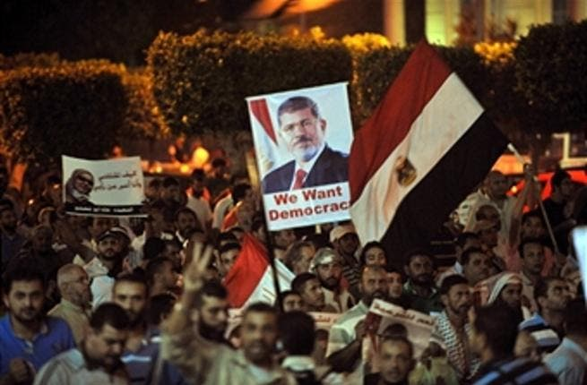 Egyptian supporters of the deposed president Mohamed Morsi hold his portrait and wave the national flags during a demonstration against the government in Cairo on July 31, 2013 ( FAYEZ NURELDINE/AFP/Getty Images)