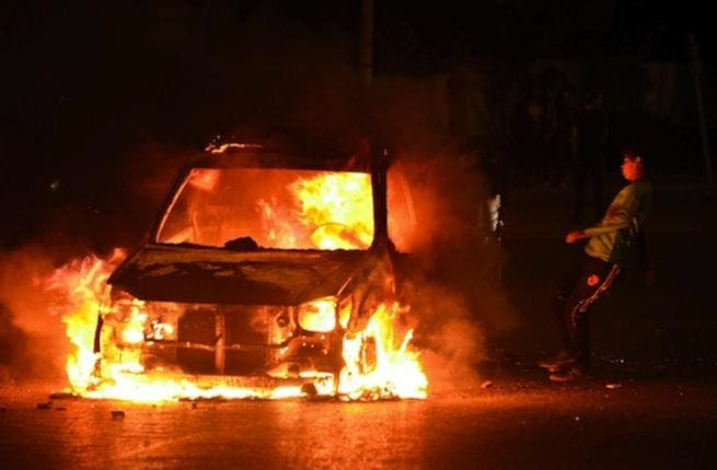 A boy kicks a burning car in Cairo on Friday as violent protests erupted between the police and those who oppose Mohamed Morsi's regime