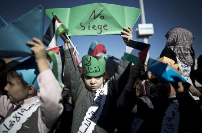 A Palestinian child raises up a paper ship reading 'No siege' during a rally to protest against the Israeli siege of the Gaza Strip on November 30, 2013 at Gaza City harbour. [Mahmud Hams/AFP]