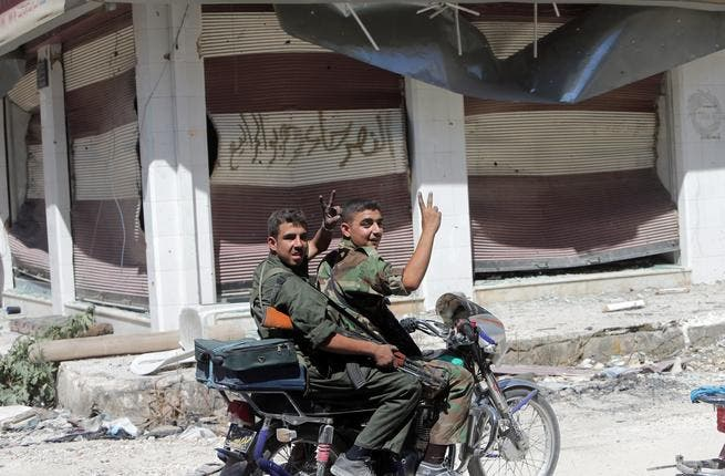 Syrian government forces flash the sign for victory as they patrol in the al-Khalidiyah district of Syria's central city of Homs by motorbike (AFP/JOSEPH EID)