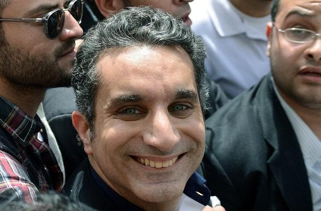 Bassem Youssef grins as he enters court to face charges brought by the state's prosecutor-general (AFP)