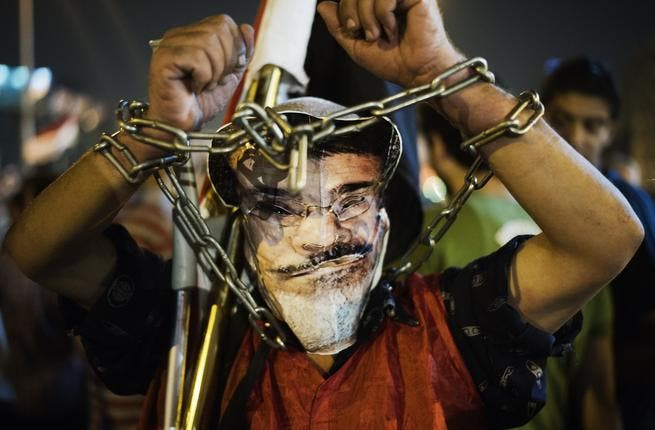 EGYPT, Cairo : A chained protester wearing a picture of President Morsi poses as hundreds of Egyptian anti-government protesters shout political slogans against Egyptian President Mohammed Morsi in Egypt's landmark Tahrir square as they watch Morsi's speech protesting against government and the Muslim Brotherhood on June 26. (AFP)