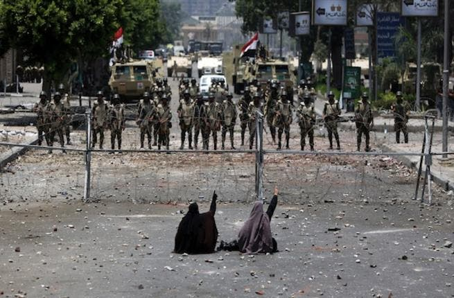 Two veiled Egyptian women, supporters of deposed president Mohamed Morsi, sit in front police standing behind barbed wire fencing that blocks the access to the headquarters of the Republican Guard in Cairo on July 8, 2013. (AFP)
