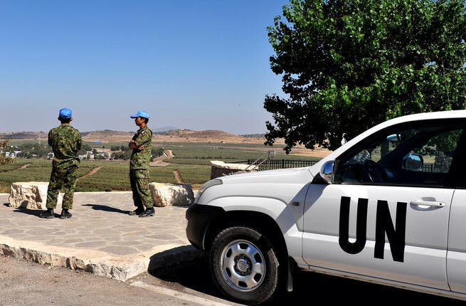 UN soldiers examine the Israeli-Syrian border on August (Shutterstock/ChameleonsEye)