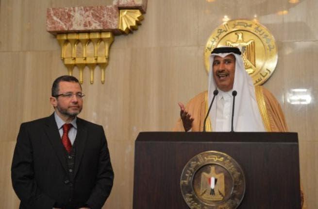 Egypt Prime Minister Hisham Qandil with Qatar's Premier and Foreign Minister Sheikh Hamad bin Jassem bin Jabr al-Thani in Doha