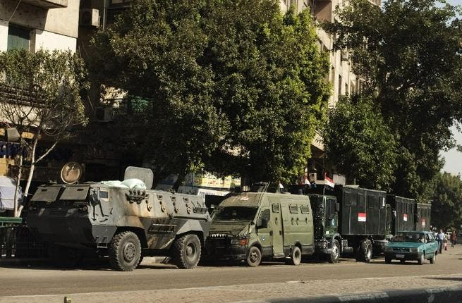 EGYPT, Cairo : Trucks and APC's of Egyptian riot police are parked in the main street leading to Egypt's landmark Tahrir square on August 20, 2013 in Cairo, Egypt.AFP PHOTO/GIANLUIGI GUERCIA