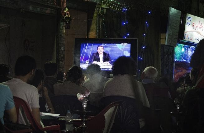 A file picture shows Egyptians watching comedian Bassem Youssef's show as they sit at a public coffee shop.  (Image credit: AFP)