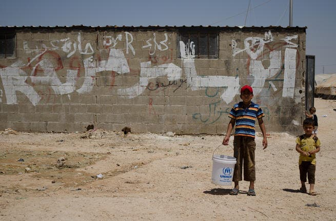 A young boy and his brother carry water to their tents in front of a wall covered in graffiti. (AlBawaba/J. Zach Hollo)