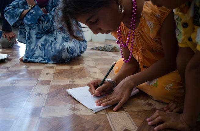 Childhood dreams: Maryam al-Lubad, 10, draws arabic letters on a notebook with her five-year-old brother Ahmad. Maryam loves calligraphy and drawing. Someday, she hopes to be an artist. (AlBawaba/J. Zach Hollo)