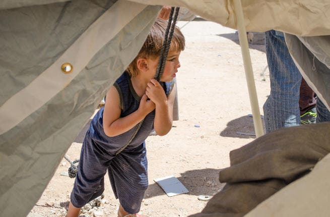 A flimsy foundation for the children of the crisis: A child leans against a rope supporting a newly assembled tent at Zaatari. (AlBawaba/J. Zach Hollo)