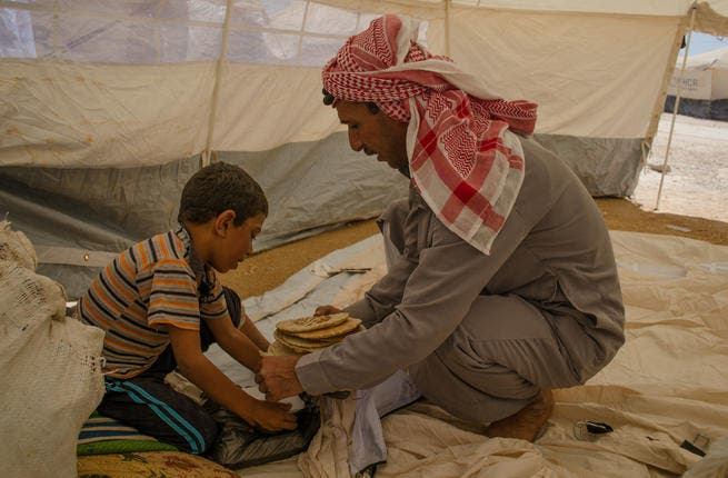 Breaking bread in the makeshift home: A father and son prepare for lunch in their tent, as camp residents scramble what little they have together. (AlBawaba/J. Zach Hollo)