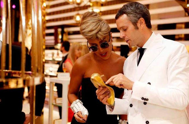 Maya Diab inspecting her gold-plated shoe (Image: Facebook)