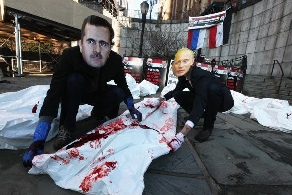 Activists dress up as the Syrian and Russian presidents