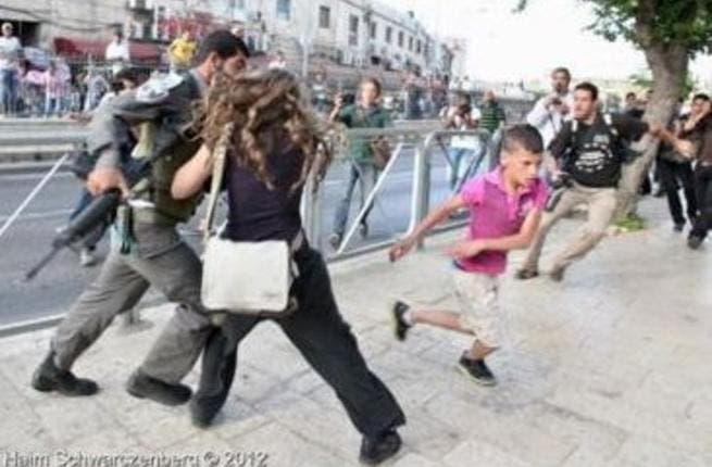 Sahar defending the boy from the Israeli soldier
