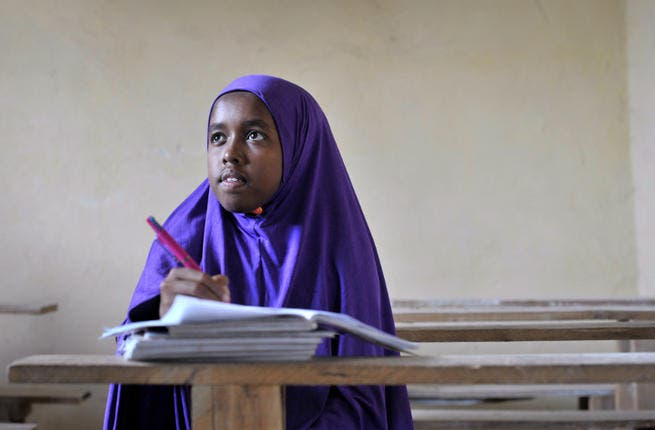 A student wearing a hijab takes notes in her exercise book (Image for illustrative purposes - Credit: AFP)