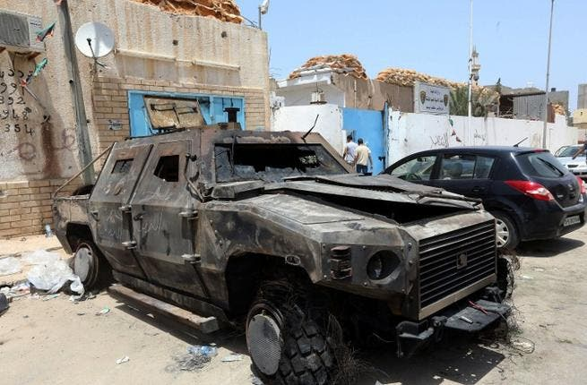 The wreckage of burnt vehicles and ransacked buildings are seen the day after deadly clashes at the Abu Salim police station on June 27, 2013 in Tripoli (Mahmud Turkia / AFP)