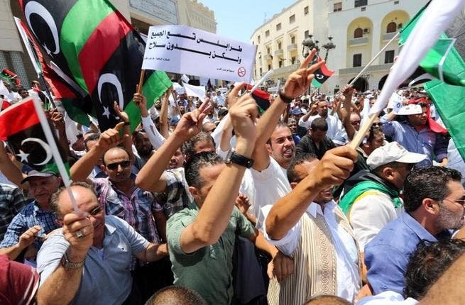 Protesters shout slogans waving national flags during a demonstration on Algeria Square to demand the removal of arms and the evacuation of unofficial armed groups on July 7, 2013 in the Libyan capital Tripoli.(MAHMUD TURKIA /AFP)