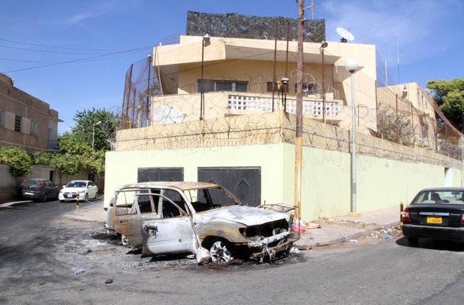 A picture taken on outside the Russian embassy in Tripoli shows a car that was destroyed during an attack. Russia has evacuated all embassy staff from Libya. (Image credit: AFP)