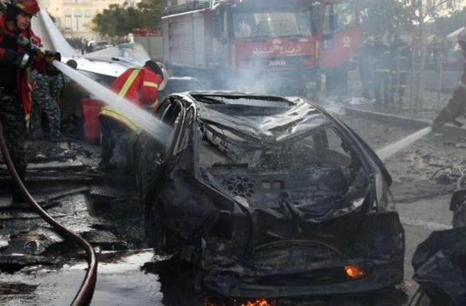 Lebanese douse a burring vehicle set ablaze by a massive car bomb explosion that rocked central Beirut on December 27, 2013. [AFP]