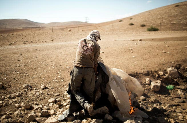 A Palestinian man burns the remains of his previous encampment, in the Jordan Valley settlement of Makhoul September 25, 2013.  The land was closed to Palestinians after Israel declared it a