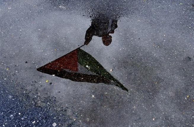A Turkish boy refleced in a puddle of water as he waves a Palestinian flag during the arrival of Turkish ship Mavi Marmara at Istanbul's Sarayburnu port, on December 26, 2010. The Israeli navy raided on May 31, 2010 the Turkish ship Mavi Marmara, which was part of a flotilla of aid ships bound for Gaza, killing several passengers and sparking international outrage.