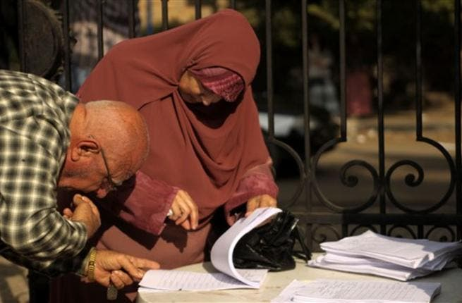 EGYPT, Cairo : An Egyptian man checks for the name of his wife at the entrance of a polling station in Cairo on November 28, 2010, as polls opened across Egypt for a parliamentary election expected to strengthen the ruling party's grip in the most populous Arab nation but marred by a crackdown on the Islamist opposition.