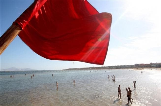 A red flag serving as a warning of shark sightings flutters over tourists enjoying a day on the beach in the Red Sea resort of Sharm el-Sheikh on December 8, 2010