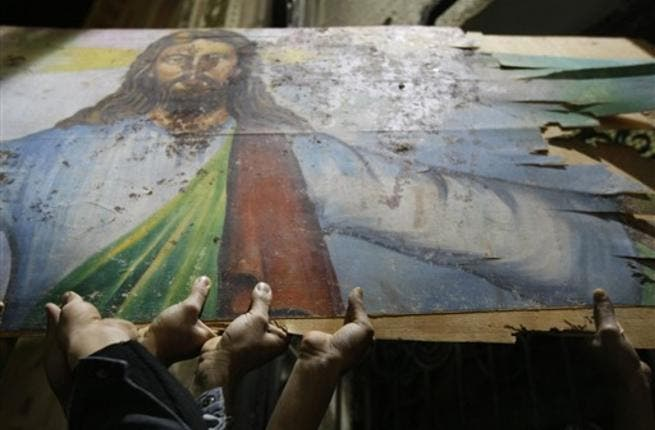 Egyptian Christians hold a blood-stained portrait of Jesus Christ during a protest late on January 2, 2011 outside the Al-Qiddissine (The Saints) church in Alexandria, following a New Year's Eve car bomb attack on the Coptic church in the northern Egyptian city in which 21 people were killed.
