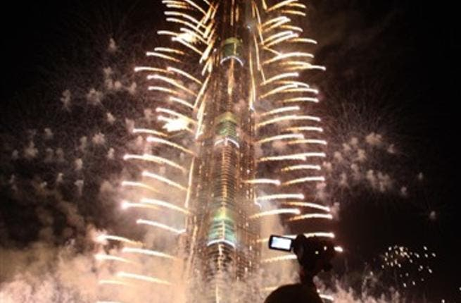 Crowds look at fireworks bursting around Burj Khalifa, the tallest building in the world, marking the New Year at midnight on January 1, 2011 in the Gulf emirate of Dubai.