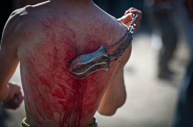 An Afghan Shiite Muslim man beats himself with chains and blades during a Muslim ritual on the last day of Ashura celebrations in the streets of Kabul on December 16, 2010.