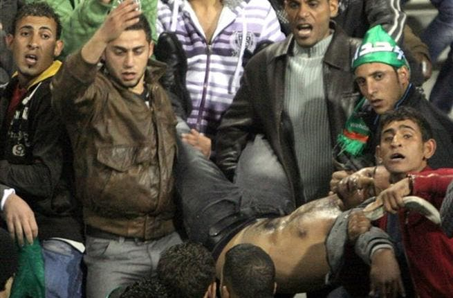 Jordanians carry a football fan injured during clashes following the Jordanian professional league football match between Al-Wihdat and Al-Faisali in east Amman on December 10, 2010