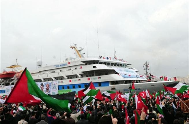 People wave Palestinian and Turkish flags as they welcome the Mavi Marmara ship at Istanbul's Sarayburnu port on December 26, 2010. The Turkish ferry which was the target of a deadly raid by Israeli commandos when it tried to deliver aid to Gaza received a rapturous welcome from thousands on Sunday as it arrived back in Istanbul.