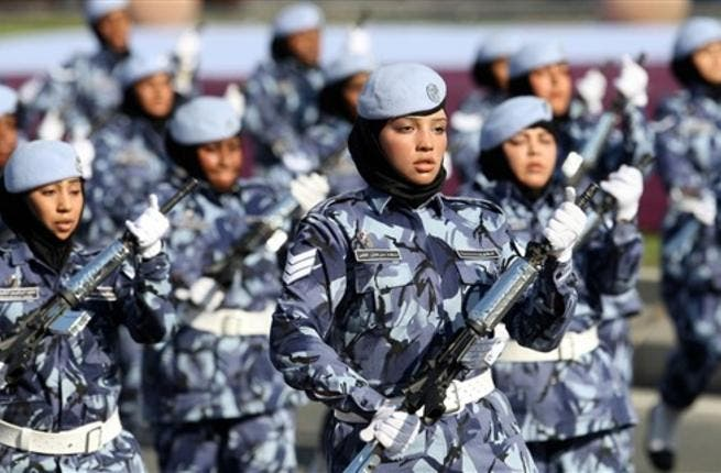 Qatari women and members of the armed forces take part in a military parade during National Day celebrations in Doha on December 18, 2010