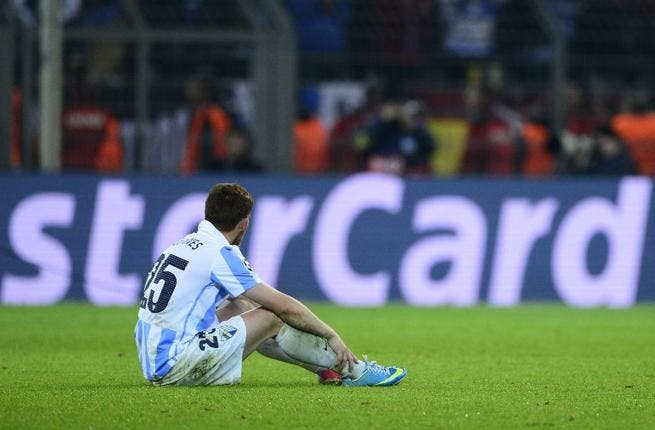 Malaga player slumps after the controversial Champions League defeat (AFP/John MacDougall)