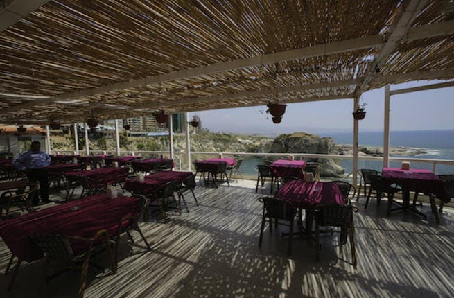 Empty tables are seen in a restaurant on the Beirut's corniche, with a sea view of the capital's landmark Pigeon's Rock, which was once crowded by tourists mainly from the Gulf states at this time of the year (Source: AFP/JOSEPH EID)