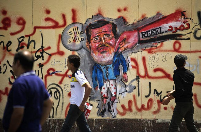 Egyptian protesters walk past graffiti against President Mohamed Morsi on the wall of the presidential palace in Cairo on July 1, 2013. (Source: AFP/GIANLUIGI GUERCIA)
