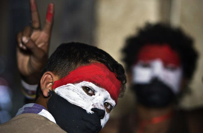 Egyptian youth with their faces painted in the colours of the national flag look on as opponents of Egyptian President Mohamed Morsi protest calling for his ouster at Cairo's landmark Tahrir Square (Source: AFP/KHALED DESOUKI)