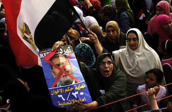 Opposition protesters shout slogans and show a defaced poster of their president as they gather in thousands at the Presidential Palace to protest against Egyptian President Mohamed Morsi and the Muslim Brotherhood (Source: AFP/GIANLUIGI GUERCIA)