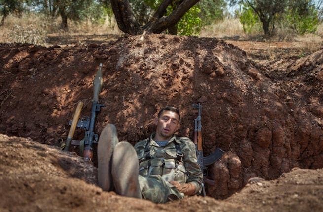 A rebel fighter takes a nap after his night shift in a trench along the highway that connects Idlib city with Latakia, 100m away from the Syrian regime's forces's positions, on July 15, 2013. (Source: AFP/DANIEL LEAL OLIVAS)