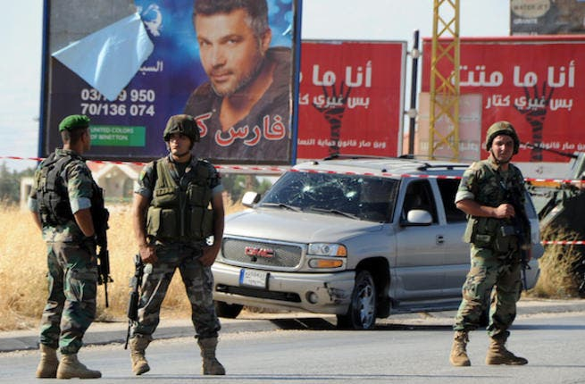 Lebanese soldiers stand guard at the site of a car bomb attack that hit a Hezbollah convoy travelling towards the Lebanese border crossing with Syria, on the Majdal Anjar-Masnaa road on July 16, 2013. (Source: AFP/STR)