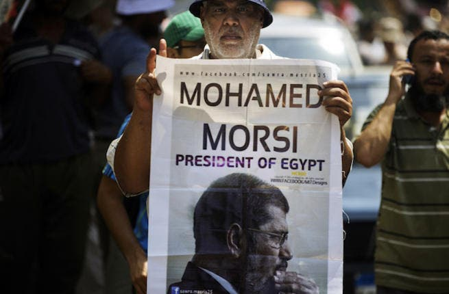A man holds a portrait of ousted president Mohamed Morsi as thousands of his supporters demonstrate for his reinstatement close to the Egyptian cabinet headquarters on July 17, 2013 in Cairo. (Source: AFP/GIANLUIGI GUERCIA)