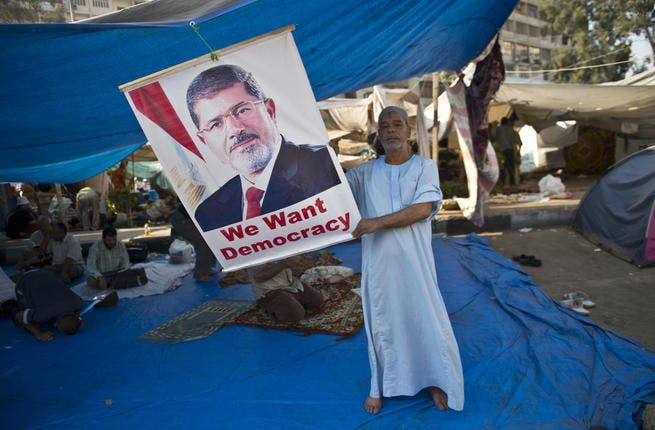 An Egyptian holds a portrait of deposed president Mohamed Morsi during a continiuing sit-in in his support outside Rabaa al-Adawiya mosque in Cairo (AFP/KHALED DESOUKI)