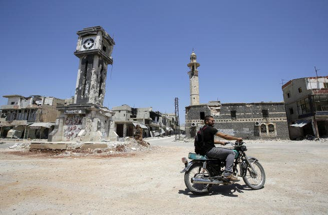 A Syrian man rides his motorbike past the Sunni Grand mosque in the city of Qusayr, in Syria's central Homs province. (AFP/JOSEPH EID)