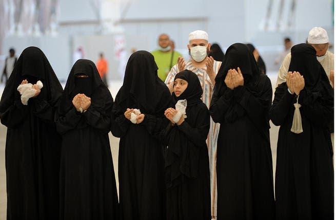 Muslim pilgrims recite prayers after throwing pebbles at pillars in the