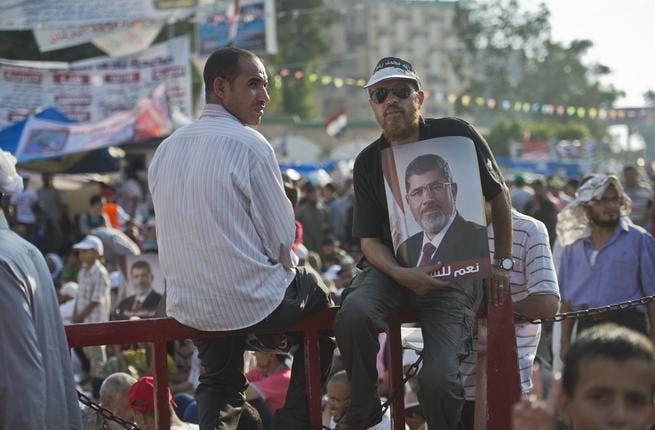 A man holds a portrait of deposed president Mohamed Morsi during a rally in his support outside Rabaa al-Adawiya mosque in Cairo (AFP/KHALED DESOUKI)