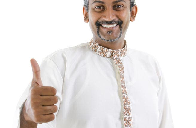 Excited thumb up Indian man in traditional costume kurta dhoti (Shutterstock/szefei)